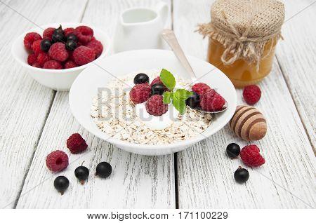 Morning breakfast - cereal yogurt fresh berries and honey on wooden background