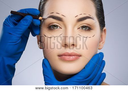 Plastic surgeon drawing dashed lines around eyes of girl, above her eyebrow. Hands in blue glove holding pencil and face. Plastic surgery, beauty portrait, closeup