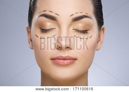 Dashed lines around eyes of girl. Beautiful girl with closed eyes. Perfect skin. Plastic surgery, beauty portrait, closeup