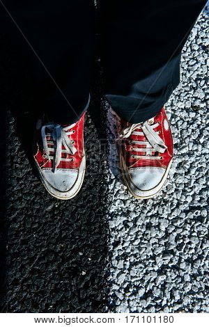 pair red shoe on the pavement. Black asphalt texture