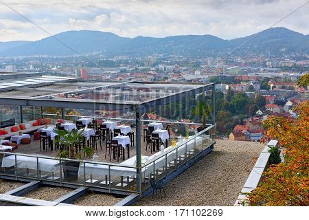 GRAZ/ AUSTRIA - OCTOBER 8. City overview from the hill Schlossberg with a restaurant in the foreground on October 8, 2016 in city of Graz, Austria.