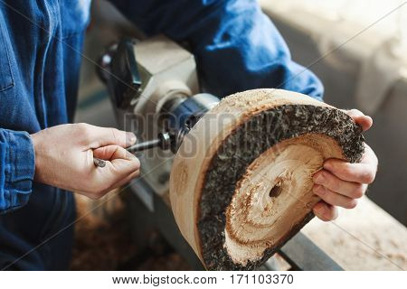 Worker's hands in  blue jeans suit working with woodcarving machine and wood, close up, point of view.