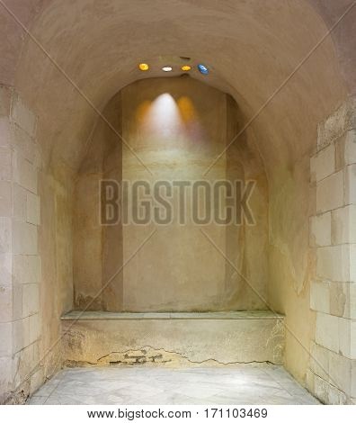 Arched stone wall lighted by colored circular shaped roof holes at a historical traditional Turkish style bath (Hamam Inal) Medieval Cairo Egypt