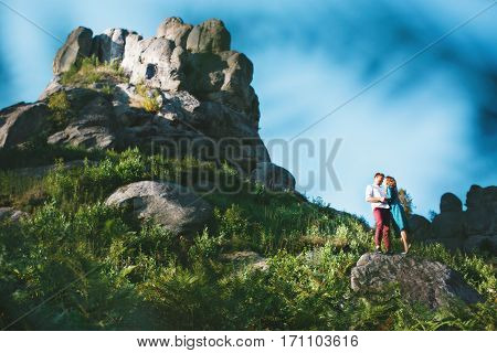 Couple standing on the small rock, outdoor. There a big rock near them. Spectacular view, nature, grass. Sunny day, summer, blue sky. Beloved looking at each other, holding hands of each other and smiling. Girl wearing blue dress and light blue shoes and
