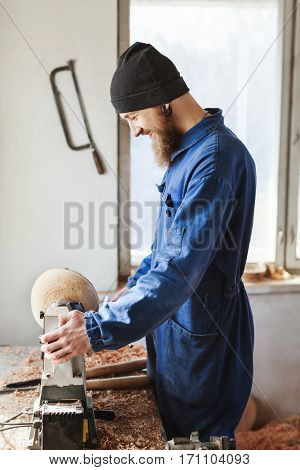 Man with a beard wearing blue jeans suit and black hat working near table, woodcarving instruments on table, big window at background.