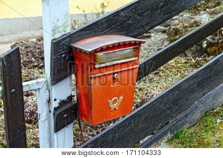 Old red mailbox on a wooden fence. Austria.