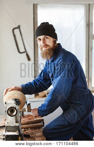 A portrait of worker with a beard wearing blue jeans suit and black hat working near table, woodcarving instruments on table and on wall, window at background.