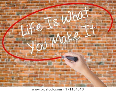 Woman Hand Writing Life Is What You Make It With Black Marker On Visual Screen