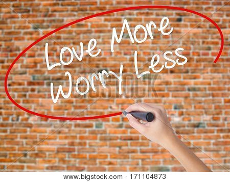 Woman Hand Writing Love More Worry Less With Black Marker On Visual Screen.