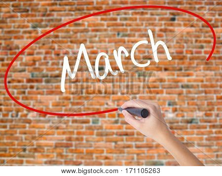 Woman Hand Writing March With Black Marker On Visual Screen