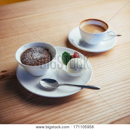 Cake ice cream with chocolate and cappuccino in the background