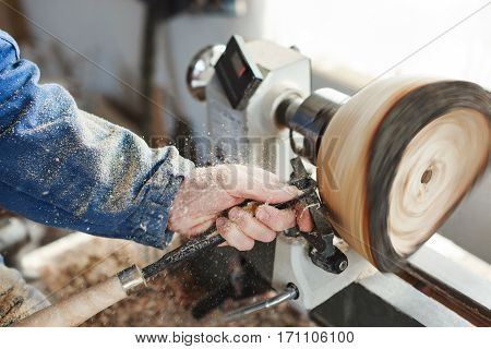 Man's hands in  blue jeans suit working with woodcarving machine, instruments and wood, shavings on table, close up, woodworking.