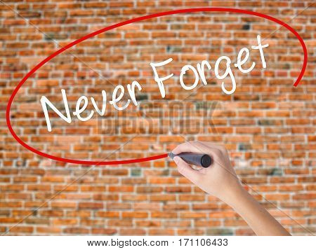 Woman Hand Writing Never Forget  With Black Marker On Visual Screen