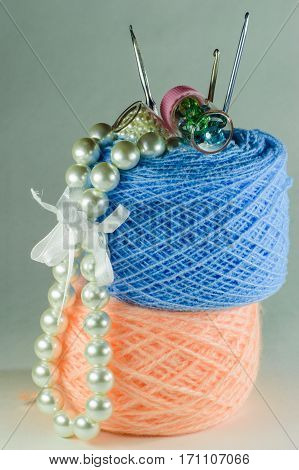 Pearl Beads, Two Small Jars With Beads, Three Hooks For Knitting And Balls Of Yarn.