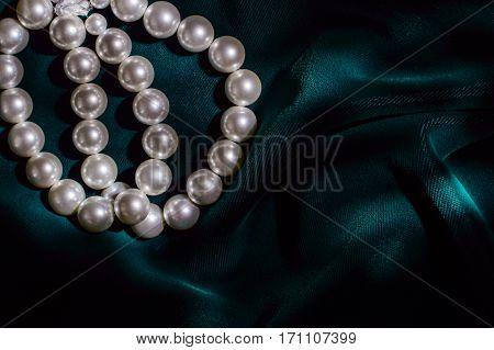 White pearl bracelet on dark green velvet top left.
