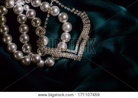 White pearl bracelet and necklace brilliant on dark green velvet.