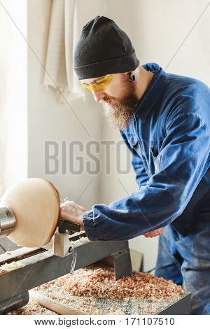 Worker with a beard wearing blue jeans suit, black hat and protecting yellow glasses working with woodcarving machine, white wall  at background, woodworking.
