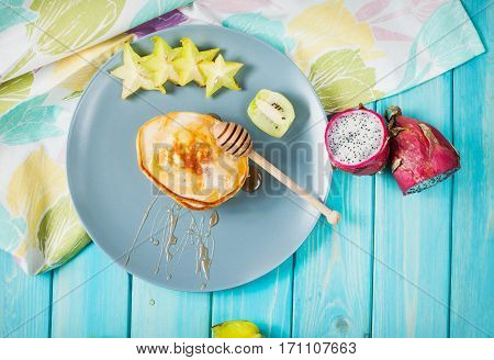 Pancakes with fruits on blue wood plate