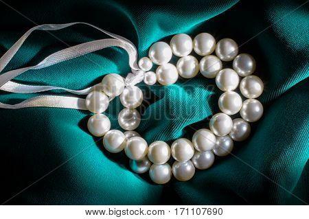 White pearl bracelet with a white ribbons on dark green velvet.