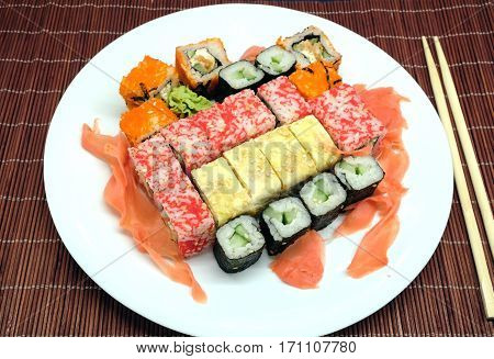 Sushi pieces on white plate and two chopsticks over brown wicker straw mat top view closeup