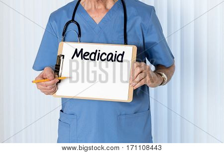 Senior male caucasian doctor with stethoscope in medical scrubs and holding clipboard for Medicaid message with pencil for emphasis