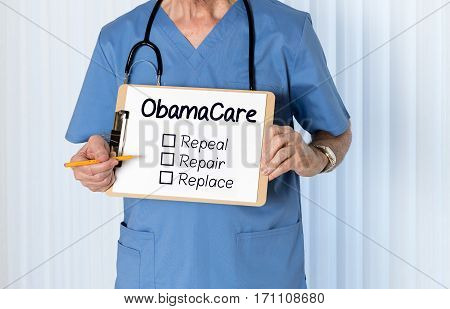 Senior male caucasian doctor with stethoscope in medical scrubs and holding clipboard for Obamacare message with pencil for emphasis