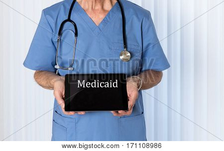 Senior male caucasian doctor with stethoscope in medical scrubs looking up and holding electronic tablet for Medicaid message