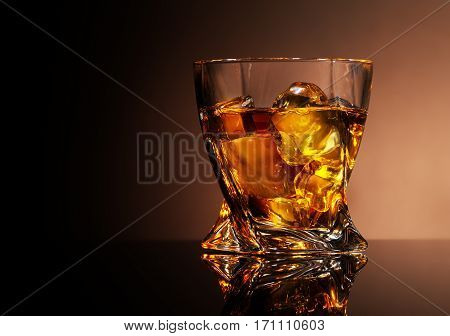 Glass of golden brandy on a brown background