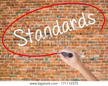 Woman Hand Writing Standards With Black Marker On Visual Screen