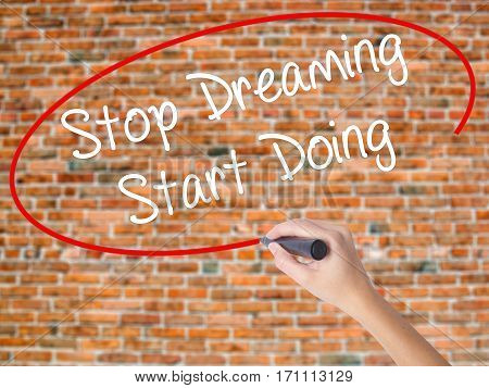 Woman Hand Writing Stop Dreaming Start Doing  With Black Marker On Visual Screen