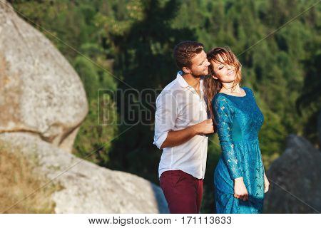 Nice couple standing together near rock, outdoor, in the countryside. Girl has closed eyes and smiling and man standing behind her with closed eyes and smiling too. Woman wearing blue dress and man wearing white shirt and claret trousers