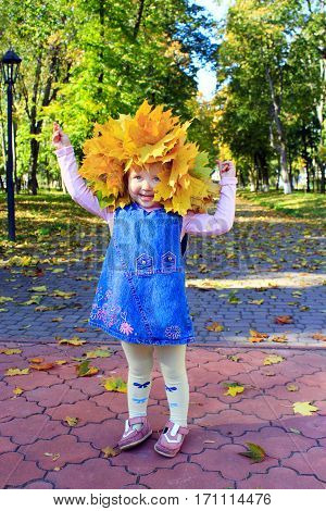baby plays with yellow Autumn leaves in the park