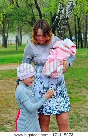 happy mother with her elder daughter look through the photo of newborn made by phone
