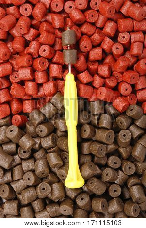 Yellow stinger needle and brown with red pre-drilled halibut pellets for carp fishing background