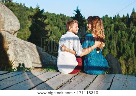 Cute couple sitting on a wooden path near rocks. Man looking at his girlfriend and she has closed eyes. Nice beloved embracing each other by one hand. Woman wearing blue dress and man wearing white shirt and claret trousers. Profile
