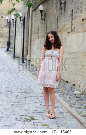Full length portrait of curlie young girl wearing biege romantic dress strolling through old streets of Inner City of Baku