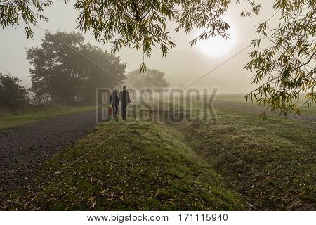 Couple waking in the fog. Taken on an autumn foggy morning in forest land with beautiful muted greens of the grass and trees.