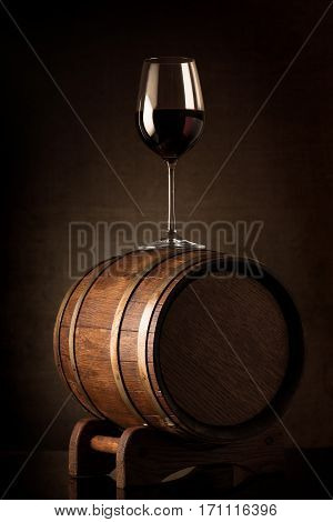 Wineglass with red wine on a wooden barrel