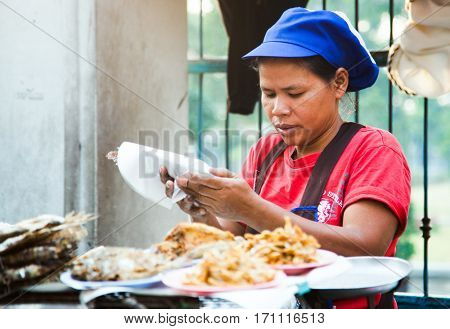 BANGKOK, THAILAND - JANUARY 24: Unknown vendor prepares and sells food on the street on Jan 24, 2014 in Bangkok, Thailand. Government figures indicate more 16,000 registered street vendors in Thailand