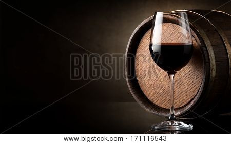 Wineglass of red wine and barrel on brown background