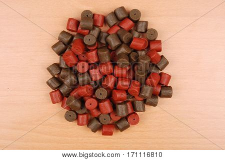 Brown with red pre-drilled halibut pellets for carp fishing isolated on wood background with soft shadow