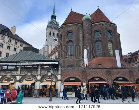MUNICH - FEBRUARY 9, 2017: Pedestrians browse shops and stalls beneath St. Peter's Church Peterskirche along Viktualienmarkt market street in Munich, Bavaria, Germany.