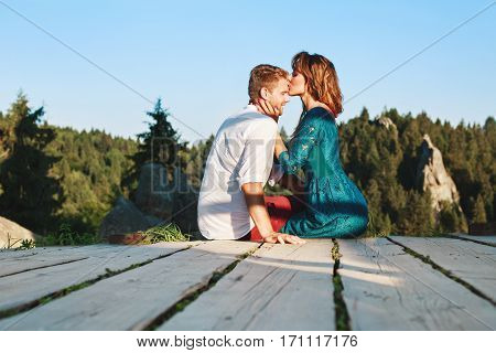 Cute couple sitting on a wooden path in the countryside, outside. Woman kissing forehead of her boyfriend and holding his head by both hands. Woman wearing blue dress and man wearing white shirt and claret trousers. Profile