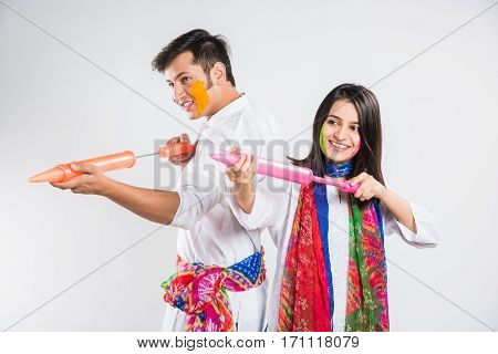 young indian couple holding pichkari on Holi festival, standing isolated over white background with copy space
