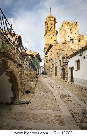 a street and the parish church in Iglesuela del Cid town, province of Teruel, Aragon, Spain