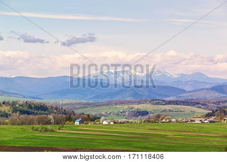 Spring fields and orchard blossom on foothills. Sunny green spring landscape. Spring fields and blooming trees. Village and town behind foothills