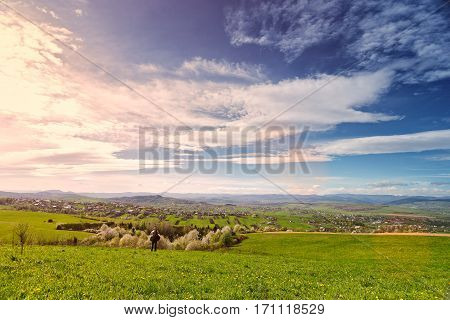 Traveler on green spring meadow. Village on sunny green spring foothills. Orchard blooming on hills. Sunny green blooming spring landscape.