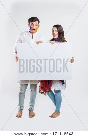 Portrait of a smart young indian couple pointing to or holding a white board on holi festival, standing isolated over white background with copy space