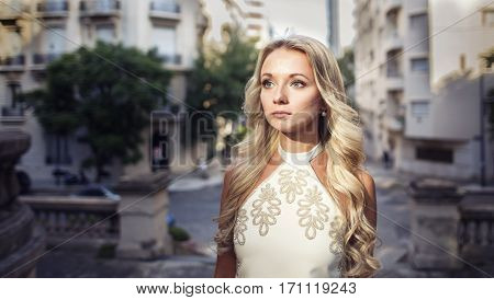 Portrait of beautiful blonde girl in white dress looking up in the old city. Perfect hair and skin. Natural make-up.