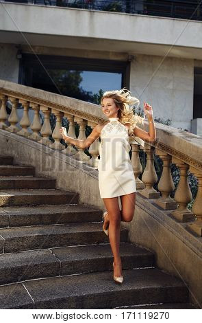 Beautiful happy blonde girl in white dress running down the stair and laughing outdoors in the city summer day